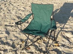 Das Bild zeigt einen faltbaren Beachstuhl im Sand.
