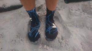 Auf dem Bild sieht man 2 Füße im Sand, welche Vincere Beachsocken zum Schutz vor Kälte tragen.