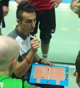 Das Foto zeigt einen Trainer mit einem Taktikboard während eines Volleyballspiels, auf dem er seinen Spielern letzte taktische Anweisungen gibt.