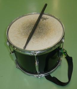 """Das Bild zeigt eine schwarze Fantrommel (12"""") mit Remo-Schlagfell und einen Drumstick aus Carbon"""