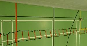 Das Bild zeigt eine schwarze Koordinationsleiter (Trainingsleiter) mit roten Sprossen