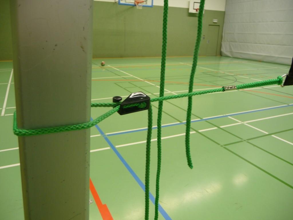 Das Bild zeigt die klassischen grünen Spannseile für das Strafziehen des Volleyballnetzes am Pfosten.