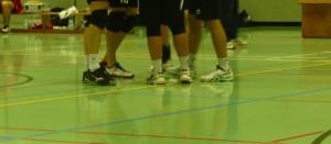 Das Bild zeigt einen Kreis von Volleyballspielern, wo man nur deren Volleyballschuhe sieht.