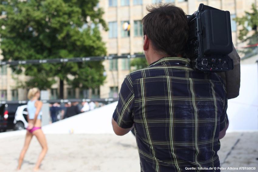 Das Bild zeigt einen Kameramann, welcher ein Beachvolleyballspiel der Smart-Beachtour filmt.