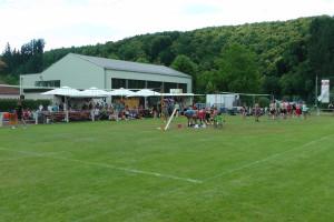 Das Bild zeigt 2 Volleyballspielfelder auf den Bettingen Open. Im Hintergrund sieht man den Bierwagen und Grillstand.