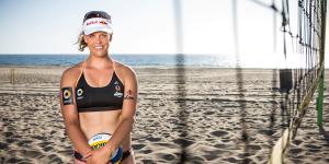 Das Foto zeigt Beachvolleyballerin und Blockspezialistin Britta Büthe hinter einem Beachvolleyballnetz am Strand. Vor dem Körper hält sie einen Mikasa Beachvolleyball.