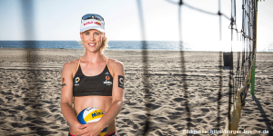 Das Foto zeigt Beachvolleyballerin und Abwehrspezialistin Karla Borgerhinter einem Beachvolleyballnetz am Strand. Vor dem Körper hält sie einen Mikasa Beachvolleyball.