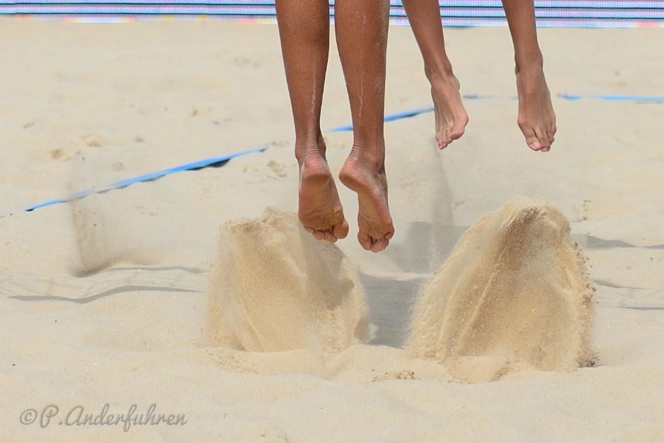 4 Füße von 2 Beacherinnen beim Absprung im Sand auf dem Beachvolleyballfeld