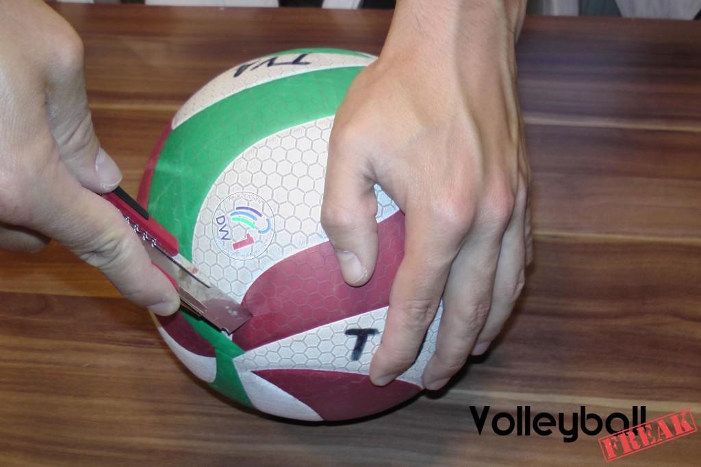 Das Bild zeigt wie der alte Molten Volleyball v5m5000 mit einem Cuttermesser angeschnitten.