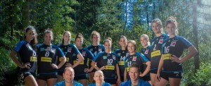 Das Teamfoto zeigt die Damen von AllgäuStrom Volleys als Mannschaft im Wald.