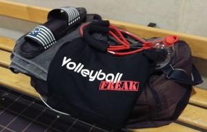 Das Foto zeigt eine gepackte Sportasche. Auf ihr ist ein VolleyballFREAK-T-Shirt. Ein Expander, Badelatschen und Handtuch.