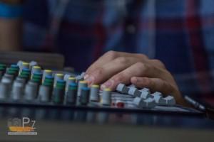 Das Foto zeigt die Hände an einem Mischpult. Dies symbolisiert einen Hallen DJ, der heizt mit Musik den Zuschauern ein.