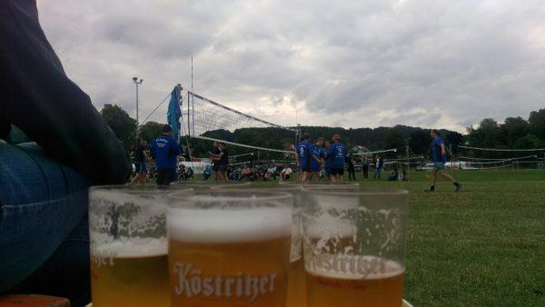 Das Foto zeigt die Biergläser für die Bierauszeit des Eröffnungsspiels auf dem Otto Scharfenberg Turnier, welches im Hintergrund zu sehen ist.