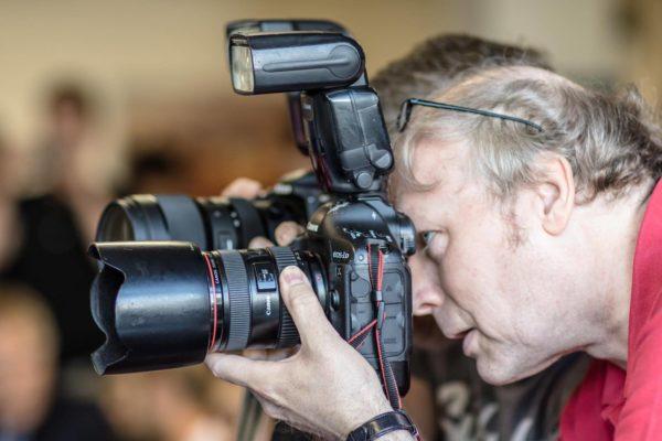 Das Foto zeigt einen Volleyball Fotografen mit einer hochwertigen Canon Fotokamera.