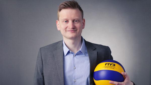Das Foto zeigt Social Media-Verantwortlicher des DVV: Lars Gäbler im grauen Anzug und blauen Hemd. In der linken Hand hält er einen blau gelben Mikasa Volleyball MVA 300.