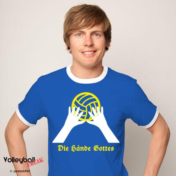 Das Foto zeigt einen Mann im blauen T-Shirt mit dem Volleyballmotive Hände Gottes