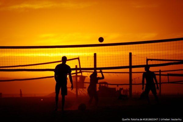 Das Foto zeigt 3 Beachvolleyballer beim Spielen im Sonnenuntergang am Strand.