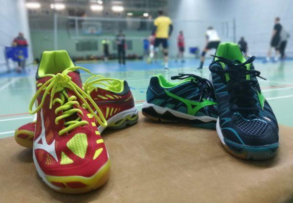 Das Foto zeigt neue Volleyballschuhe 2018: Mizunos Wave Lightning Z4 und Wave Tornado X2. Im Hintergrund trainiert eine Volleyballmannschaft.