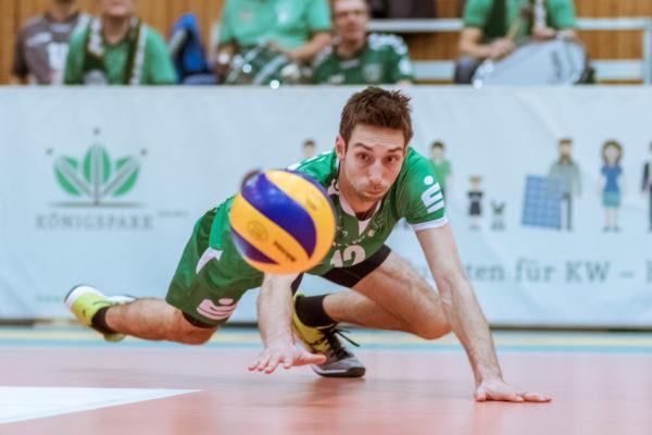 Daniel Heinecke versucht den blau-gelben Mikasa Volleyball noch abzuwehren indem er seine flache Hand zwischen Ball und Boden schiebt.