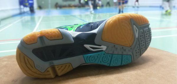 Das Foto zeigt die Sohle vom Volleyballschuh Sohle vom Mizuno Wave Tornado X2. Im Hintergrund sind unscharf Volleyballspieler beim Training zu sehen.