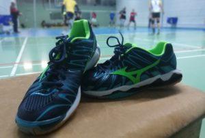 Das Foto zeigt die Die Mizuno Wave Tornado Wave X2 in blau/grün. Im Hintergrund sieht man ein Volleyballfeld, wo das Training läuft.