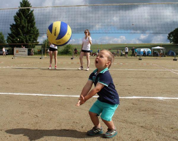 Kind versucht einen Mikasa Volleyball zu baggern.