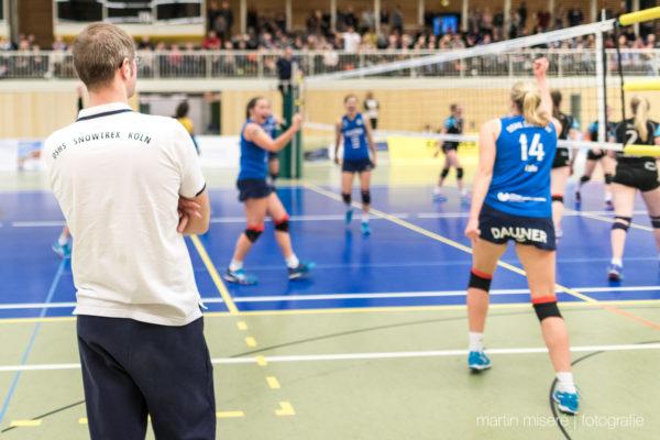 Jimmy Czimek mit verschränkten Armen im Vordergrund. Im Hintergrund spielt die 1. Damenmannschaft DSHS Snowtrex Köln.