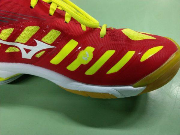 Das Foto zeigt den roten Mizuno Wave Lightning Z4 mit einem kleinen Schaden durch das Training.