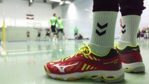 Das Foto zeigt die roten Mizuno Wave Lightning Z4 Volleyballschuhe im Vordergrund. Im Hintergrund findet ein Volleyballspiel statt.