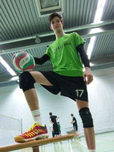 Das Foto zeigt VolleyballFREAK Oli mit den roten Mizuno Wave Lightning Z4 beim Test in der Sporthalle..Im Hintergrund sieht man ein Volleyballfeld mit Volleyballnetz und spielern.