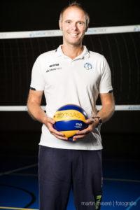 Das Foto zeigt Volleyballtrainer Dr. Jimmy Czimek vor einem Volleyballnetz mit einem blau-gelben Mikasa Volleyball in der Hand.