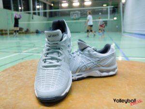 Die grauen Asics Netburner Ballistic Volleyballschuhpaar in der Frontansicht. Im Hintergrund trainieren Volleyballspielerinnen.