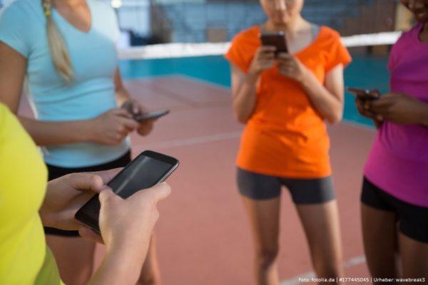 Teenager stehen vor einem Volleyballnetz und schauen auf ihr Smartphone