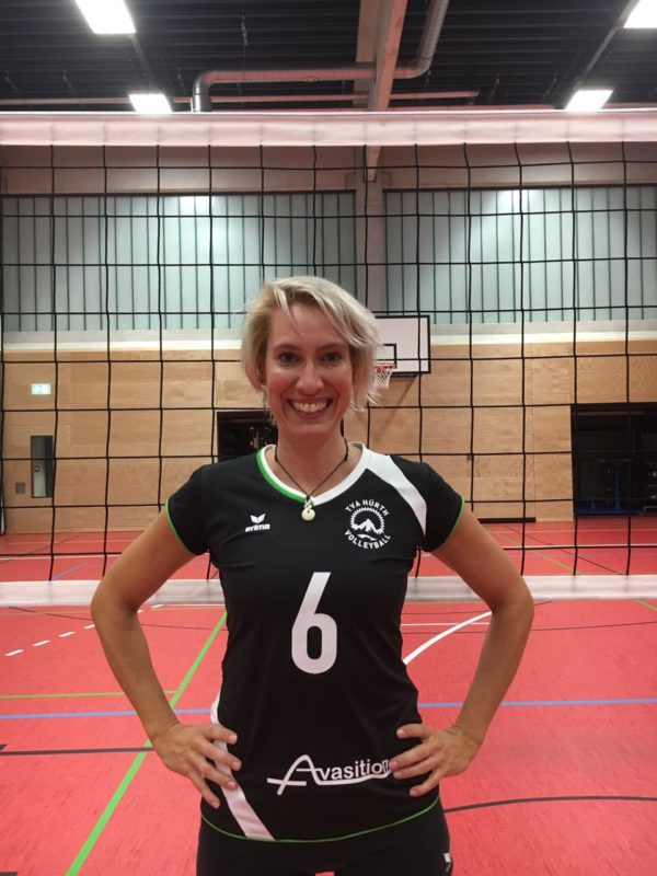 Portraitfoto einer Volleyballspielerin vor einem Netz. Aber mit dem Makel eines offenen Garagentor im Hintergrund.