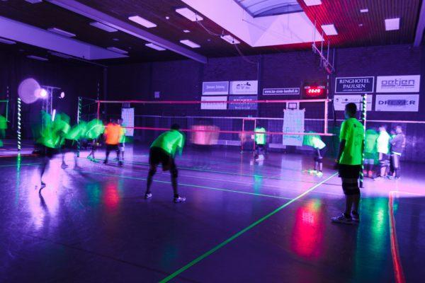 Auf dem Foto sieht man Spieler, Volleyballfeld und das Volleyballnetz beleuchtet von Schwarzlicht.