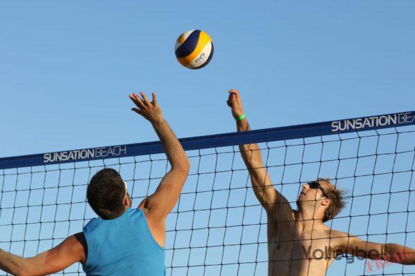 Das Foto zeigt 2 Beachvolleyballspieler im Luftduell am Beachvolleyballnetz.