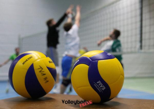 Das Foto zeigt den alten Mikasa mva200 neben dem neuen Mikasa V200w Volleyball. Im Hintergrund trainieren Volleyballer am Netz