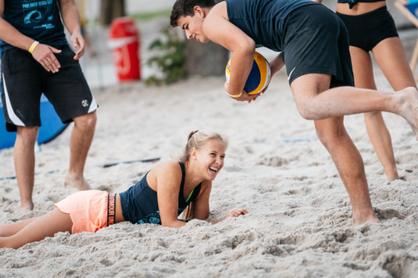 Das Foto zeigt eine Beachvolleyballspielerin lachend am Boden liegend.