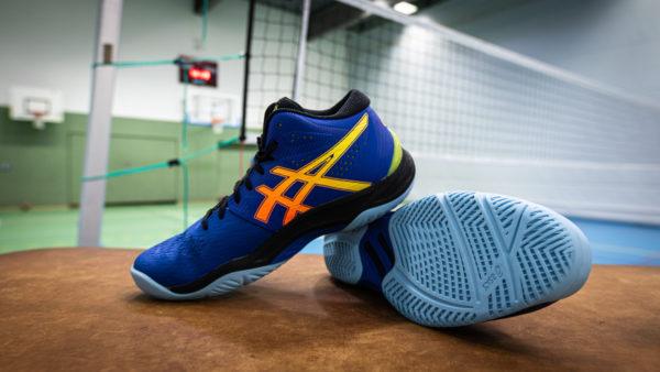 Schlichtes blaue Design mit den typischen Asics Streifen. Im Hintergrund sieht man ein gespanntes Volleyballnetz.