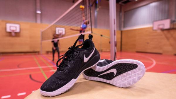 Das Foto zeigt ein Paar Nike Zoom HyperAce 2. Im Hintergrund greift ein Volleyballspieler an einem Volleyballnetz einen Mikasaball an.